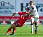 Ulster winger Craig Gilroy tries to break a tackle from the Scarlets' Hadleigh Parkers Credit: ©INPHO/Craig Thomas