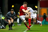 Munster flanker Jack O'Donoghue tries to keep the ball in play under pressure from Ulster's Andrew Trimble Credit: ©INPHO/James Crombie