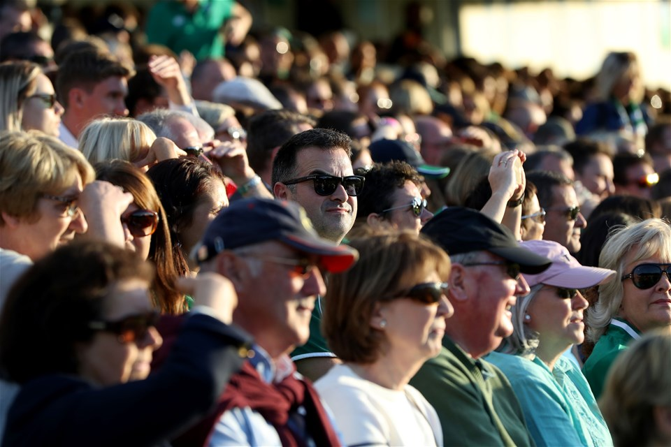Fans look on during the game which drew a large crowd to the 3,500-capacity UCD Bowl